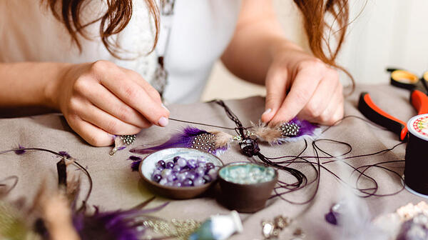 woman-making-handmade-gemstone-jewelry-home-feather-craft-ss-FEATURED